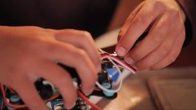 Las manos de los niños montan el quadcopter de piezas Fans de la ingeniería de radio