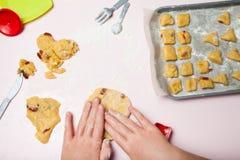 Las manos de los niños preparan las galletas deliciosas con las bayas, la visión superior Platos del juguete, el concepto de tort foto de archivo