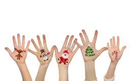 Las manos de los niños que aumentan para arriba con símbolos pintados de la Navidad Imagen de archivo