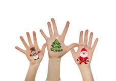 Las manos de los niños que aumentan para arriba con símbolos pintados de la Navidad: Santa Claus, árbol de navidad, hombre de la  Imagenes de archivo