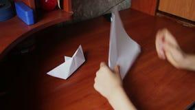 Las manos de los niños que hacen el avión de la papiroflexia almacen de metraje de vídeo