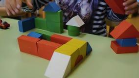 Las manos de los niños recogen los cubos brillantes del primer de madera en la tabla Pensamiento l?gico Desarrollo de ni?os prees almacen de video