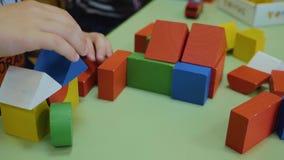 Las manos de los niños recogen los cubos brillantes del primer de madera en la tabla Pensamiento l?gico Desarrollo de ni?os prees almacen de metraje de vídeo