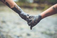 Las manos de los niños se están sosteniendo con la arcilla del fango Concepto de la ayuda Retro Fotos de archivo libres de regalías