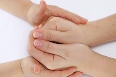 Las manos de los niños tocan al niño a la mano de su madre en un puño Foto de archivo libre de regalías