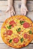 Las manos de los ni?os sostienen la pizza de queso con los tomates y la albahaca, comida en la tabla r?stica de madera, visi?n su imagen de archivo libre de regalías