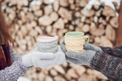 Las manos de los pares en manoplas toman las tazas con té caliente en parque del invierno fotos de archivo