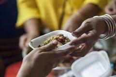 Las manos de los pobres reciben la comida de la parte dispensadora de aceite del ` s Concepto de la pobreza fotografía de archivo libre de regalías
