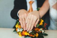 Las manos de los recienes casados con los anillos de bodas y el ramo del ` s de la novia en la tabla Imagen de archivo libre de regalías