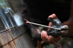 Las manos de los trabajadores están soldando con autógena Foto de archivo