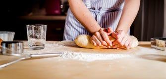 las manos de las mujeres amasan la pasta en la tabla, accesorios de la cocina Foto de archivo