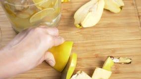 Las manos de las mujeres cortaron en los pedazos de membrillo para tomar algo hechos de la fruta c?trica hecha a mano con el jeng almacen de metraje de vídeo