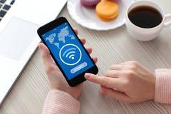 Las manos de las mujeres que llevan a cabo el uso del teléfono buscan Wi-Fi libre en pedregal imágenes de archivo libres de regalías