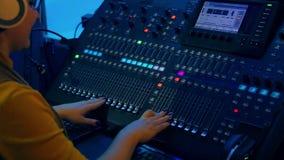 Las manos de las mujeres que trabajan en la consola de mezcla en la iluminación del color almacen de video