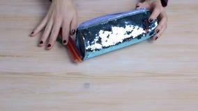Las manos de las mujeres sostienen una caja de lápiz y toman los lápices hacia fuera coloreados de ella almacen de metraje de vídeo