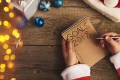 Las manos de Sata que escriben las metas por Año Nuevo Árbol de navidad y deco Imagen de archivo