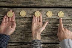 Las manos de tres hombres de negocios con Bitcoins presentaron en fila Fotos de archivo