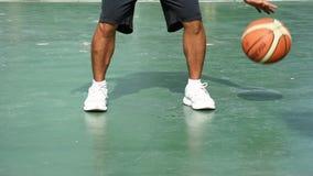 Las manos de un baloncesto del golpe del hombre en un fondo verde con la mano izquierda en el parque de BangYai, Nonthaburi en Ta almacen de metraje de vídeo