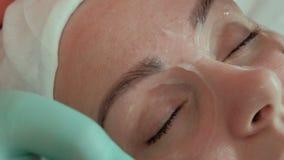 Las manos de un cosmetólogo gastan los electrodos alrededor de los ojos de una mujer joven Masaje de Microcurrent Muchacha hermos almacen de video