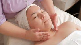 Las manos de un cosmetólogo hacer masaje facial La muchacha asiática en un salón de belleza miente con los ojos cerrados El el pr almacen de metraje de vídeo