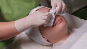 Las manos de un cosmetólogo profesional en los guantes blancos limpian la cara de una mujer musulmán relajada con los trapos cosm almacen de video