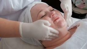 Las manos de un cosmetologist profesional aplicar una crema de alimentación o que rejuvenece en el cuello y la cara de una mujer  almacen de metraje de vídeo