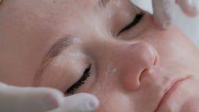 Las manos de un cosmetologist profesional en los guantes blancos están aplicando la crema del ojo alrededor de los ojos femeninos almacen de metraje de vídeo