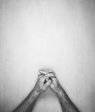 Las manos de un hombre se doblan en una cerradura en un fondo gris, visión superior Imagen de archivo libre de regalías