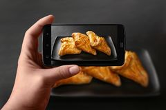 Las manos de un hombre toman las fotos de la comida en la tabla con el teléfono Bollos frescos con el relleno vegetal Pan del tr fotos de archivo