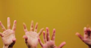 Las manos de un individuo y de una muchacha son movimiento y contracción nerviosa divertidos en un fondo amarillo aislado en estu metrajes