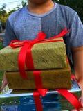 Las manos de un muchacho están sosteniendo las cajas de un regalo fotografía de archivo libre de regalías