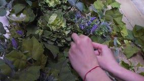 Las manos de un primer del decorador del florista, una muchacha adornan un photozone metrajes