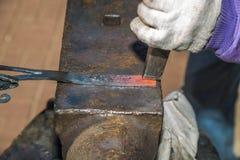 Las manos de un trabajo del herrero de fundición con un martillo en el yunque Fotos de archivo libres de regalías