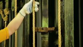 Las manos de una escena de trabajo de la mujer en guantes bajan la cortina del teatro con un cable almacen de metraje de vídeo