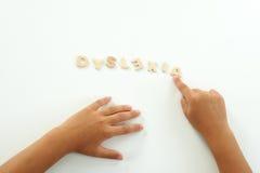 Las manos de una muchacha forman la dislexia de la palabra Foto de archivo libre de regalías