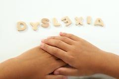 Las manos de una muchacha forman la dislexia de la palabra Fotografía de archivo libre de regalías