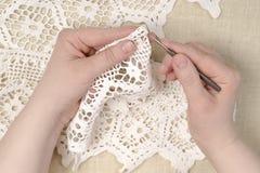Las manos de una mujer hacen punto un vestido, hilo Imágenes de archivo libres de regalías