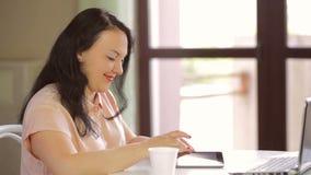 Las manos de una mujer joven en una blusa rosada están funcionando en una tableta MES lento metrajes