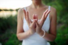 Las manos de una mujer joven se doblan de una manera especial en un yo Imagenes de archivo