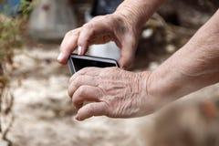 Las manos de una mujer mayor con un teléfono móvil Fotos de archivo libres de regalías