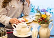 Las manos de una mujer que se sienta en una tabla con una taza de té y de macarrones en un café foto de archivo libre de regalías