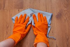 Las manos de una mujer usando los trapos azules limpian el piso de madera Imágenes de archivo libres de regalías