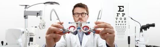 Las manos del óptico con el marco de ensayo, doctor del optometrista examinan el ojo fotografía de archivo