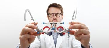 Las manos del óptico con el marco de ensayo, doctor del optometrista examinan el ojo foto de archivo libre de regalías