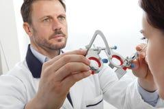 Las manos del óptico con el marco de ensayo, doctor del optometrista examinan el ojo fotos de archivo