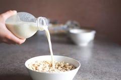 Las manos del adolescente vierten la leche de la botella plástica Foto de archivo
