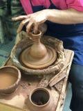 Las manos del alfarero que hace los platos de la arcilla marrón foto de archivo