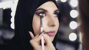 Las manos del artista de maquillaje profesional que aplica el sombreador de ojos al ` musulmán s de la mujer observan usando cepi almacen de metraje de vídeo