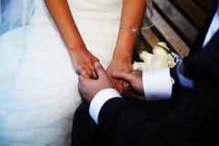 Las manos del ascendente cercano de novia y del novio Imagen de archivo libre de regalías
