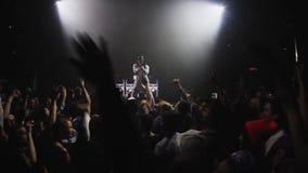 Las manos del aumento de la gente saltan en partido en club nocturno Hombre de Mc que se realiza en etapa danza almacen de metraje de vídeo